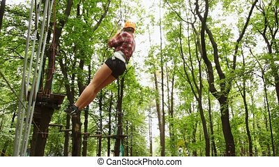 girl moves down downwards suspended on cable in wood between...