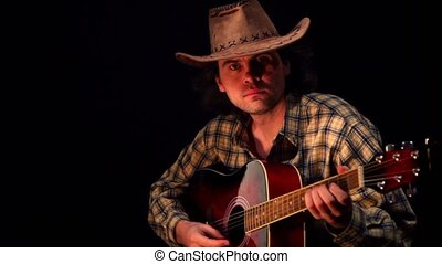 Man wearing hat and shirt in square plays guitar at dark...