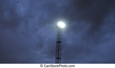 Tower with searchlight shines night sky