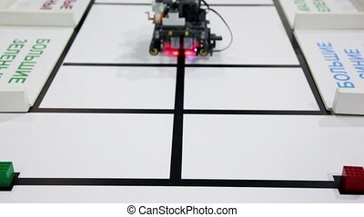 Small robot moves and take green cub, view from above