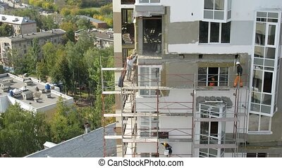 Workers build the house which stands in front of park, time...