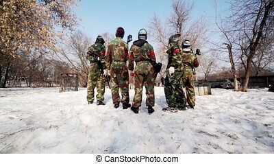 Five men paintball team stand and look on playground, view...