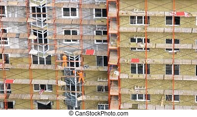 Workers stands on scaffold put window frame and glaze...