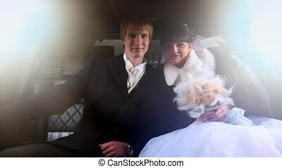 Newly-married couple sits together in limousine and kisses