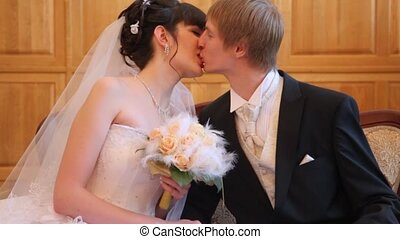 Two newly-married couple sits in registry office and kisses