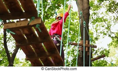 girl goes on boards suspended in wood, strong keeping for...