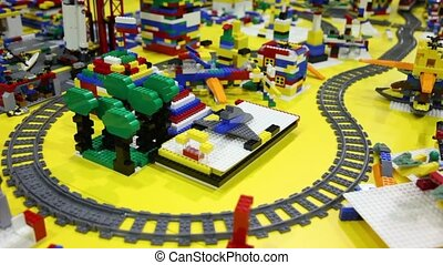 Toy train moves by railroad among different objects on...