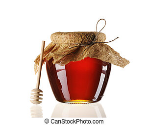 Jar of honey and dipper isolated over white