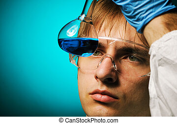 Scientist in protective wear and glasses looking at chemical...