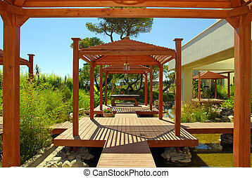 wood pavilion, deck and tropical plants in summer resort -...