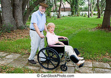 Rolling Through The Park - Disabled senior woman being...