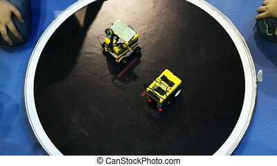 two robot toy cars competing on round platform, one pushes...