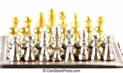 Small golden and silver chess figures in start position at...