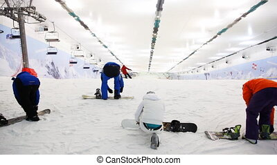 professional sportsmans with snowboard prepares for training in indoor ski