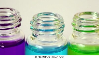 Transparent open bottles moves sideward with color ink on...