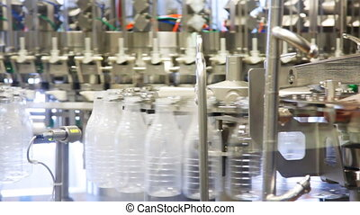 lots of bottles filled with little detergent rotated at huge milk factory