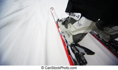 close-up of skiers legs with skis that ride on snow,...
