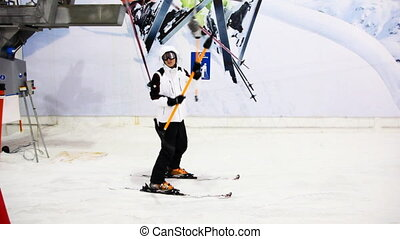 skier sportsman sitting on handle goes up hill in sport...
