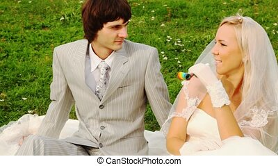 Newly-married couple sits on meadow and bride blows in party...