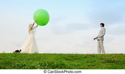 Newly-married couple throws each other big sphere, and terrier nearby runs
