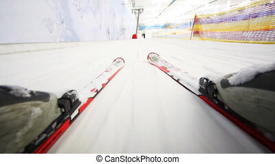 close-up of skiers legs with skis that ride on snow, camera...