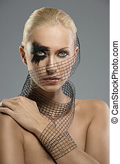 Pretty blonde girl with dark make-up and grid around the neck, the face and wrist, she looks in to the lens and her left hand is on the right shoulder