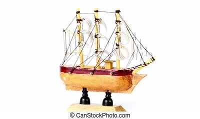 Toy wooden ship spins on prop isolated on white background