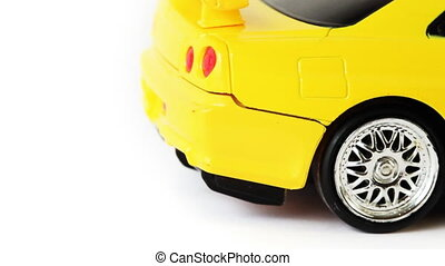 yellow toy radio-controlled car moves back and forth on...
