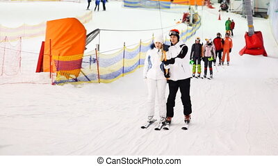 instructor with girl hold some stick and go up on hill to ski