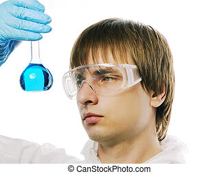 Scientist in protective wear and glasses looking at flask...