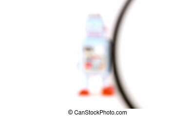 Loupe magnifies toy robot isolated on white background