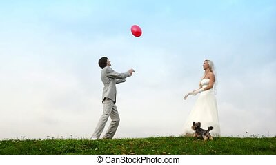 Newly-married couple throws each other an air sphere-heart, doggie runs nearby