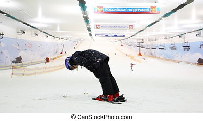 little skier boy holds balance and does some exercises on...