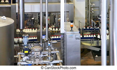 milk bottles in conveyor belts move and behind automation...