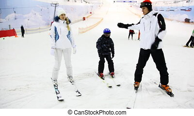 instructor shows girl and little boy some exercises on skis