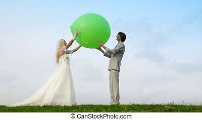 Newly-married couple throws upwards together inflatable sphere and catches it