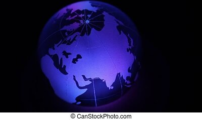Glass sphere with world map on it and color illumination at...