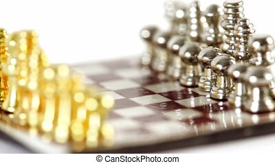Small golden and silver chess figures in start position spin...