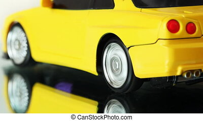 wheels of yellow toy radio-controlled car rotate back and...