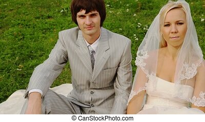 man and woman in wedding dresses sit on meadow fastened by...