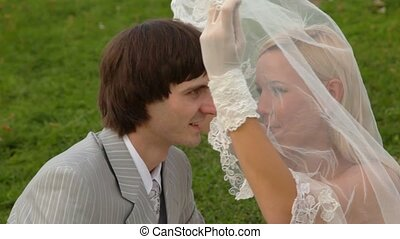 Newly-married couple sits on grass together and kisses under veil of bride