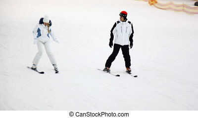 skier instructor with girl go down to ski on slope in close...