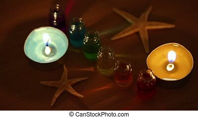 Two candles burn, six open bottles with color aroma oil and...