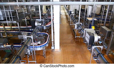 dairy factory with long zigzag moving conveyor of bottles milk