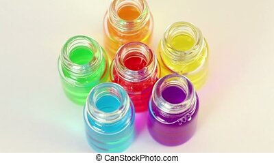Six transparent open bottles rotates with color oil on them