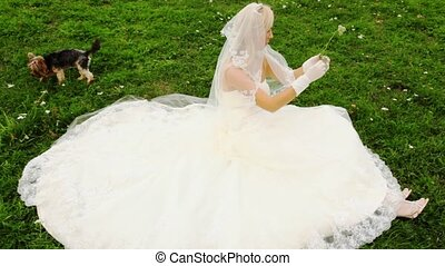 blonde in wedding dress sits on lawn and plays floret with...