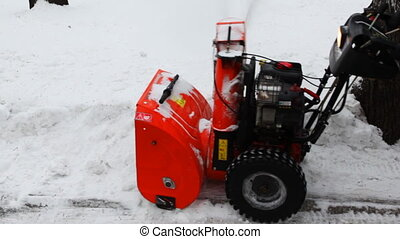 man cleans snow with small manual machines, closeup