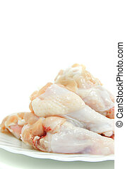 raw chicken drumstick on a white plate