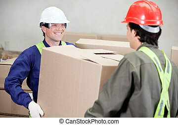 Foremen Carrying Cardboard Box At Warehouse - Two foremen...