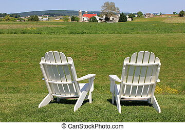 Adirondack chairs on edge of field - Two adirondack chairs...